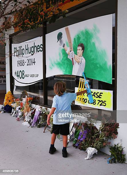 A school kid pays tribute to Phil Hughes at a shop front on December 2 2014 in Macksville Australia Cricket player Phillip Hughes passed away aged 25...