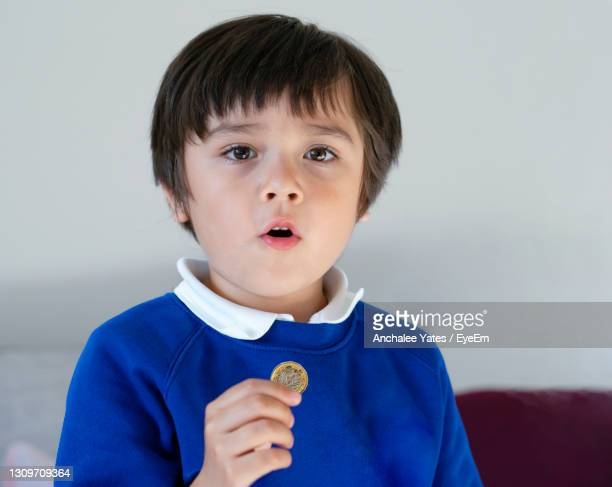 school kid showing one pound coin on his hand,child boy wearing school uniform holding money coin, - us coin stock pictures, royalty-free photos & images