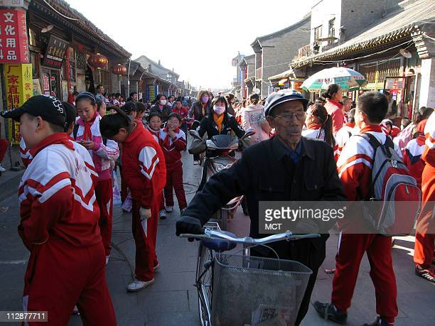 School kids and bicyclists fill a pedestrian street in Hohhot, capital of China's Inner Mongolia region.
