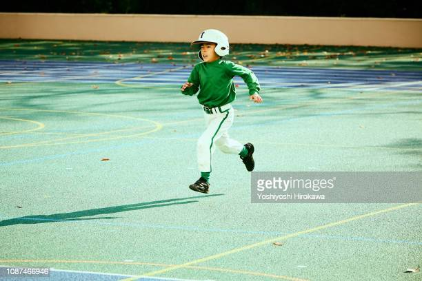 school kids (6-7) base runner running between bases in baseball game - somente japonês - fotografias e filmes do acervo