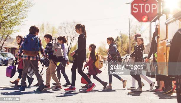 school kids crossing street - pedestrian crossing stock photos and pictures
