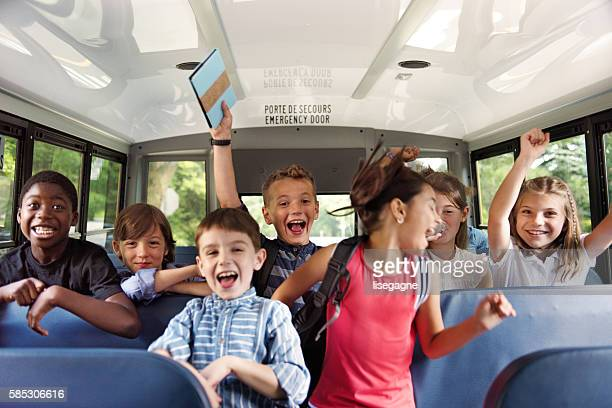 school kids gesturing on school bus - vehicle interior stock pictures, royalty-free photos & images