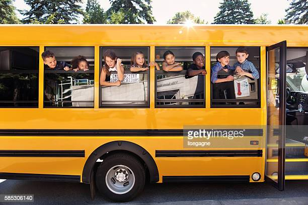 School kids hanging out bus windows