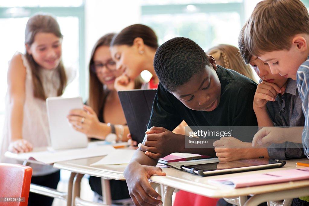 School kids in class using a digital tablet : Stockfoto