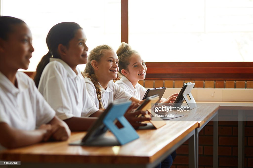 School kids in class with tablets, looking up : Stock Photo