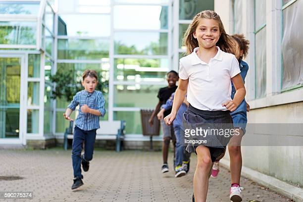 School Kids in schoolyard, running