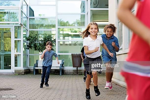 School Kids in schoolyard, running
