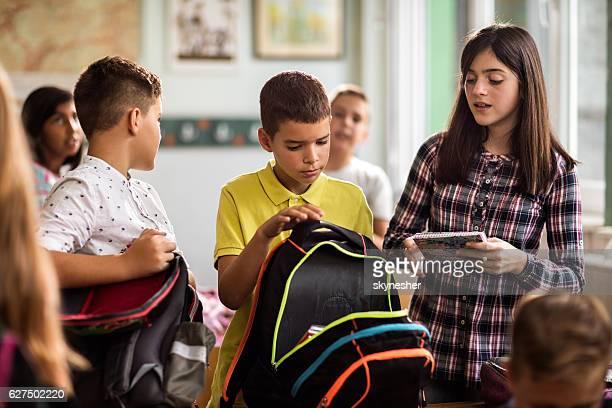 School kids packing school supplies in backpacks in the classroom.