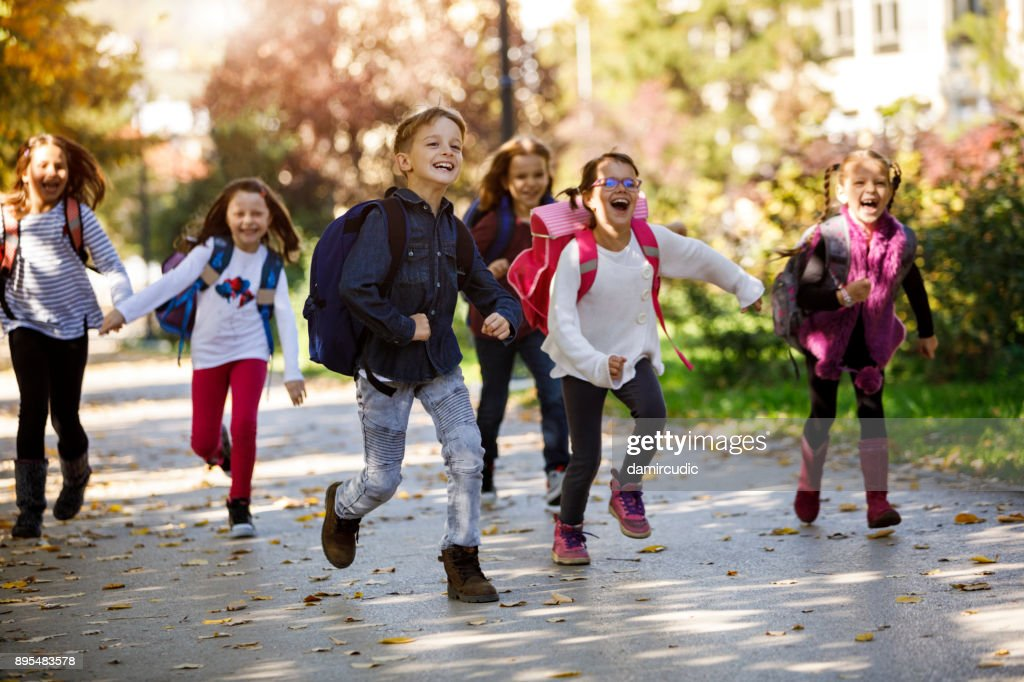 School kids running in schoolyard : Stock Photo