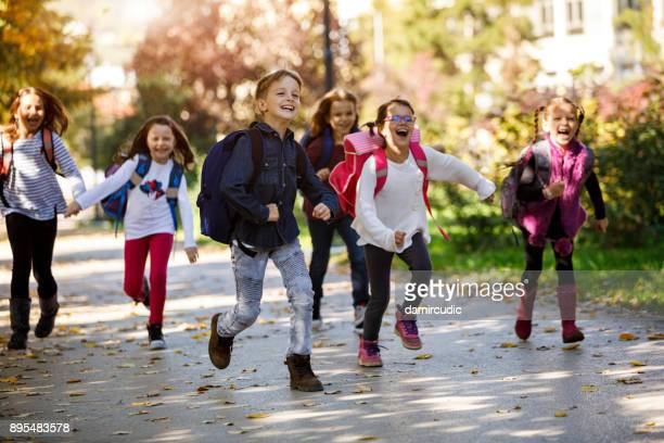 school kids running in schoolyard - schoolboy stock pictures, royalty-free photos & images