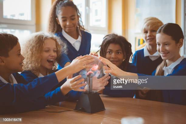school kids touching plasma ball during phisics lesson at school - physics stock pictures, royalty-free photos & images