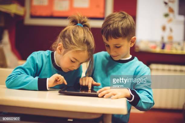 デジタル タブレットを使用して学校の子供たち - 男子生徒 ストックフォトと画像