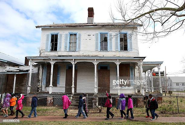 School kids walk by a vacant home that is along the historic route that civil rights marchers took during the Selma to Montgomery march on March 6...