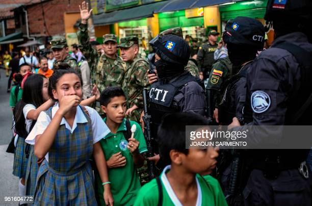 TOPSHOT School kids walk by soldiers and members of the Technical Investigation Team at the Comuna 13 neighborhood Medellin Antioquia department...