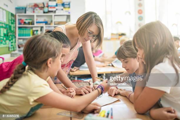 schoolkinderen werken samen aan een project - mid adult men stockfoto's en -beelden