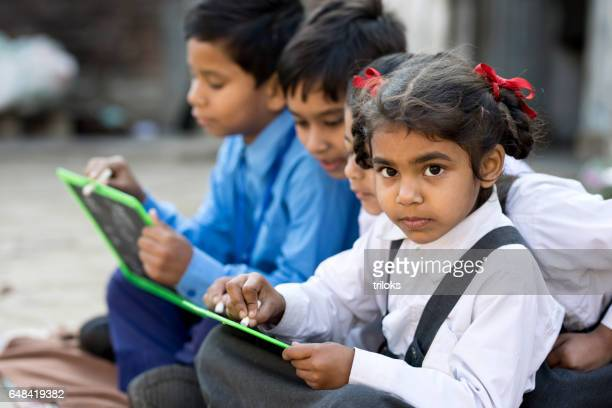 School kids writing on slate