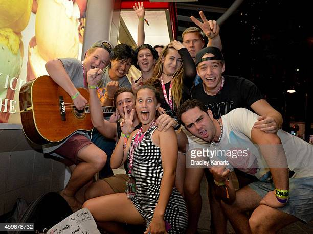 School leavers celebrate with a busker during Australian 'schoolies' celebrations following the end of the year 12 exams on November 28 2014 in Gold...