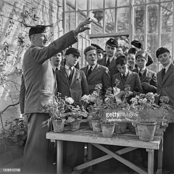 School master points out items of interest in a greenhouse to a class of junior boys in the grounds of a public school in an English town during...