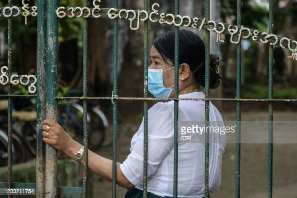 School official stands behind the entrance of a school in Sittwe, capital of western Rakhine State on June 1, 2021. - Schools in Myanmar opened on...