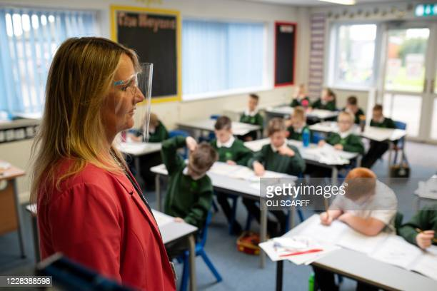 School Principal Catherine Sharpe, wearing a face visor due to the COVID-19 pandemic, observes year three and year four pupils as they are taught in...