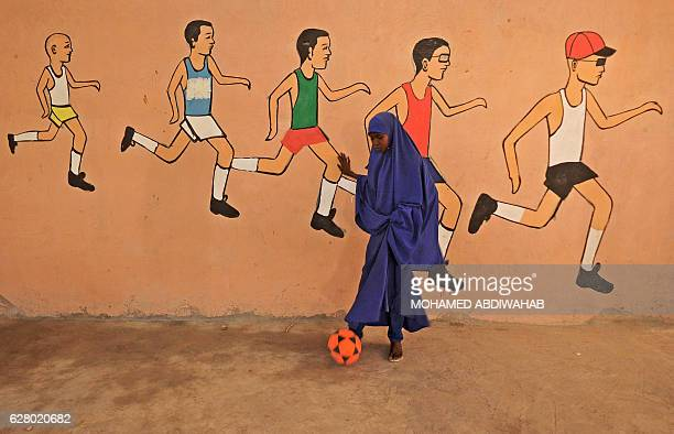 TOPSHOT A school pupil kicks a ball during a sports lesson at a school in Mogadishu on December 6 2016 / AFP / MOHAMED ABDIWAHAB