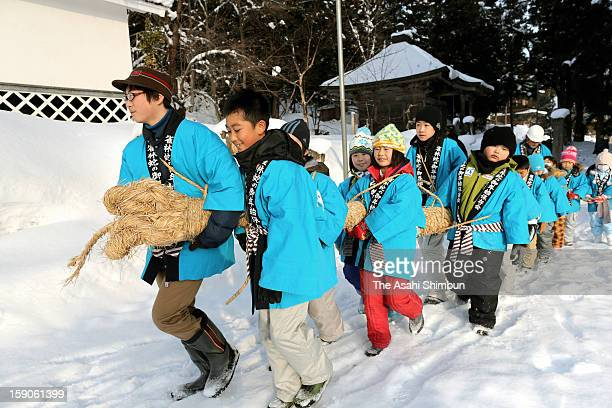 School pupils holding a 7meterlong 30kilogram straw snake walk around the town during the HebinoGonenshi or Snake's New Year on January 7 2013 in...