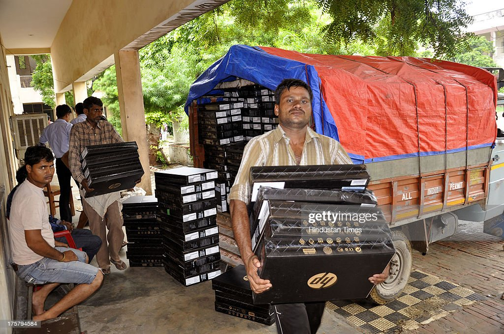 School staff carrying Laptops to be distributed to students in second-phase of distribution on August 8, 2013 in Ghaziabad, India. Around 11,000 new laptops have arrived so far. Samajwadi Party government of Uttar Pradesh is distributing free laptops to the 12th pass students as per its promise made during polls.