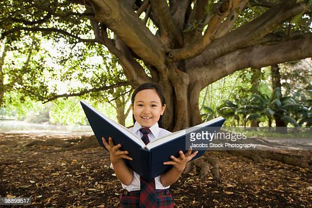 School Student Holding Book by Tree