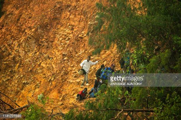 School students and staff members of St Charles Luanga walk past a mudslide on March 17 covering a major road at Skyline junction in Chimanimani...