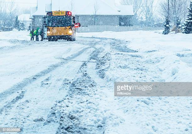 school students boarding blizzard snow storm school bus - winter weather stock photos and pictures