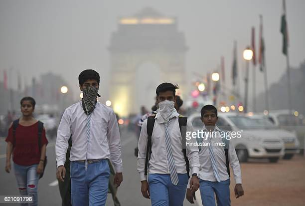 School students covers their face with a handkerchief to avoid thick smog at Janpath Market in the evening as the air quality deteriorated sharply...