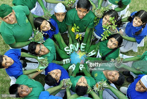 School students give a message for Save Earth during the awareness program on the eve of World Earth Day in the village of Reethkheri 15km from...