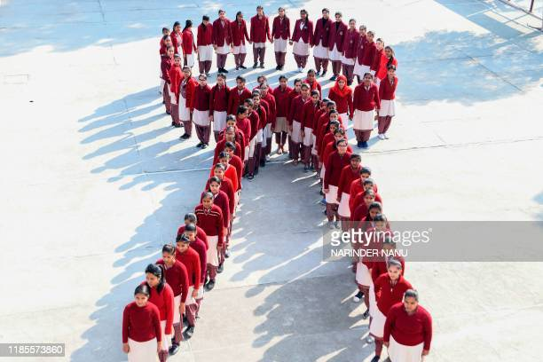 School students pose for a photograph as they stand in the shape of a ribbon as part of an awareness event on the eve of the 'World AIDS Day' in...