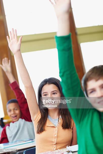 School students raising hands in classroom