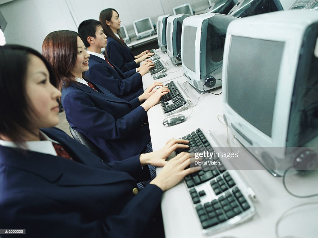 School Students Sitting in a Line and Working on Computers : Stock Photo