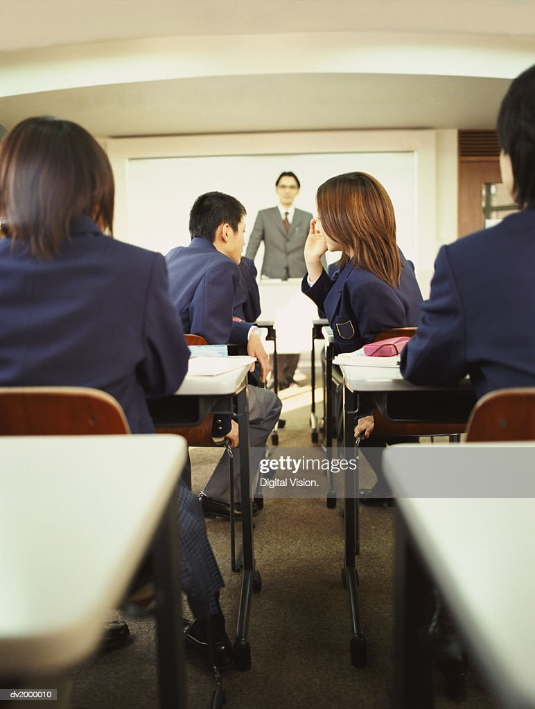School Students Whispering Together in a Classroom : Stock Photo