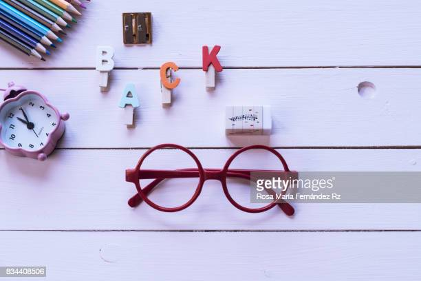 School supplies, alarm clock, word 'back' and eyeglasses on pink background with copy space