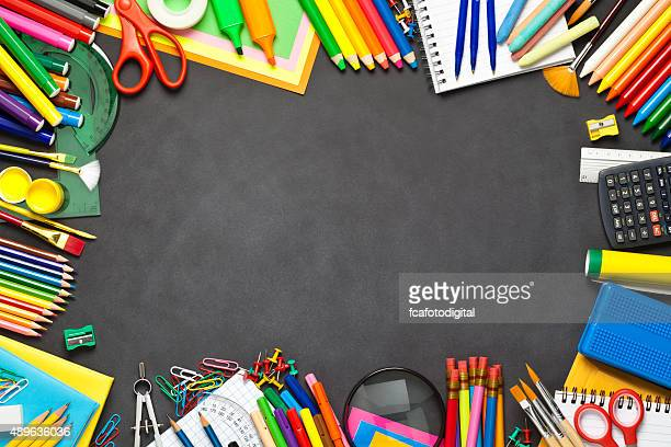 School supplies border on black chalkboard