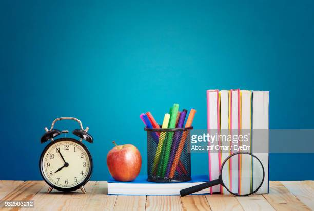 School Supplies With Apple On Table Against Blue Background
