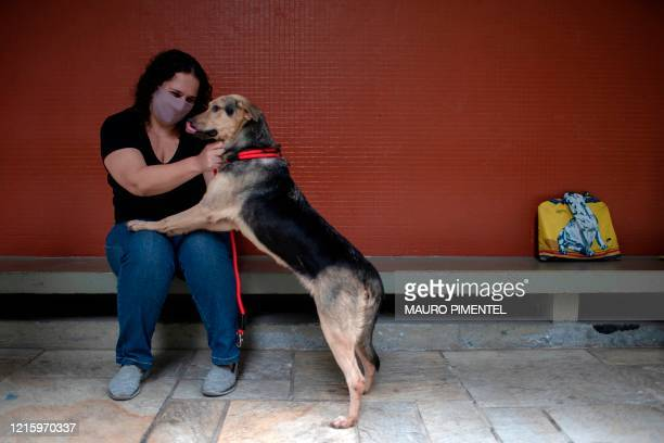 School teacher Adriana Nogueira caresses her newly adopted dog, Mabel, a tree-year-old, at her home of Lagoa neighborhood, in Rio de Janeiro, Brazil,...