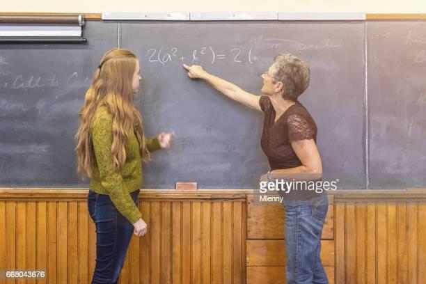 School teacher at chalkboard explaining formula to teenage student