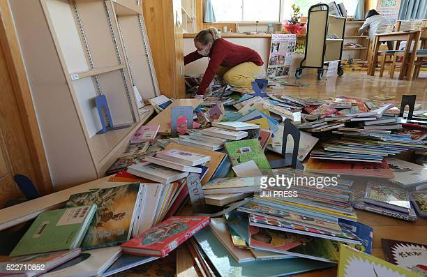 School teacher cleans scattered books caused by an earthquake at Minami-Aso Nishi elementary school in the village of Minami-Aso, Kumamoto prefecture...