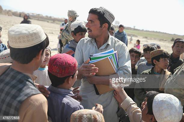 A school teacher clutches school supplies donated to his village by soldiers from the US Army's 4th squadron 2d Cavalry Regiment on February 27 2014...