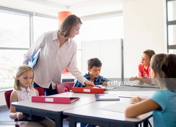 school teacher helping students in classroom - junior level stock pictures, royalty-free photos & images