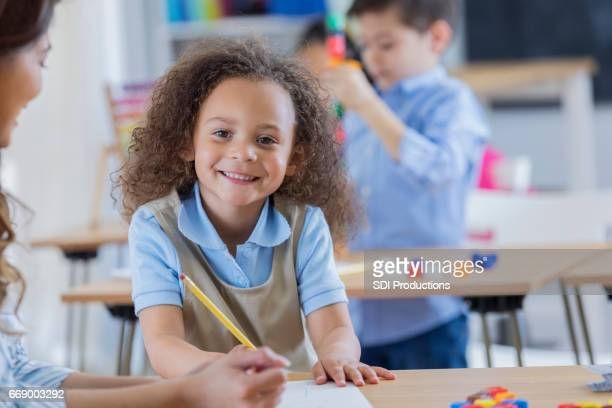 School teacher helps cheerful student