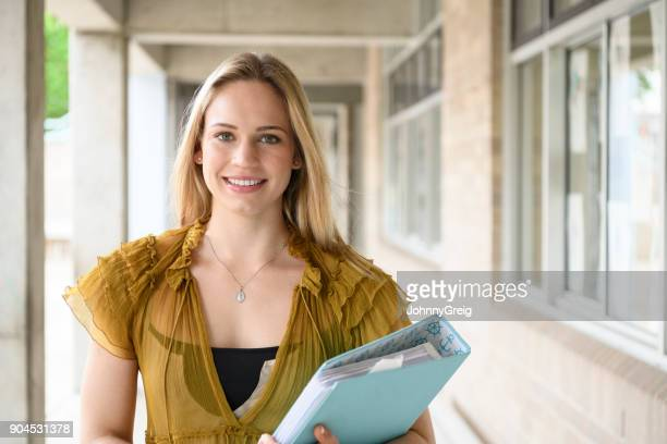 School teacher smiling towards camera with file