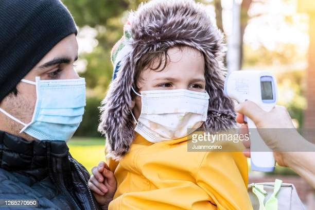 school teacher taking temperature to a little child boy before he goes back to school - bubonic plague stock pictures, royalty-free photos & images