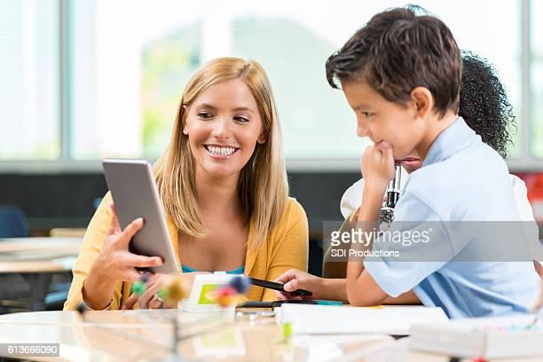 STEM school teacher uses digital tablet to help student