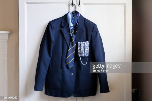 school uniform and face mask for use during covid 19 coronavirus pandemic - schuluniform stock-fotos und bilder