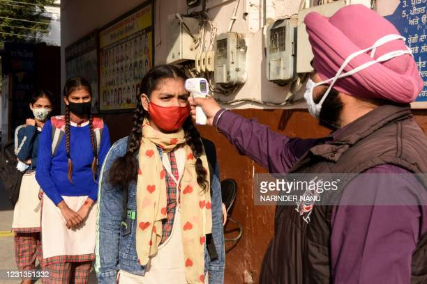 School worker checks the body temperature of student as they arrive at a government girls school amid the ongoing Covid-19 coronavirus disease...